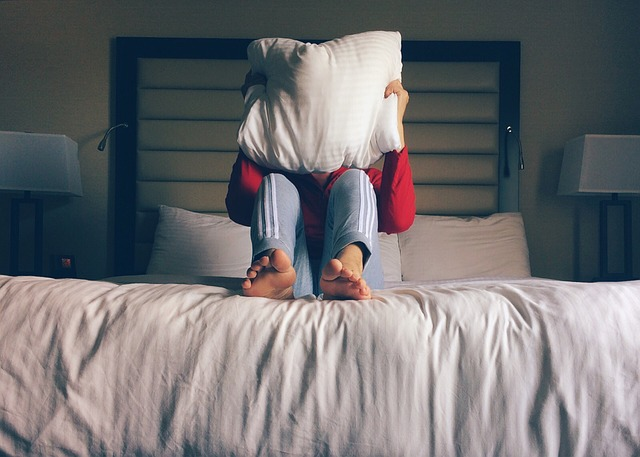 Dítě sedící na posteli, držící si před obličejem polštář