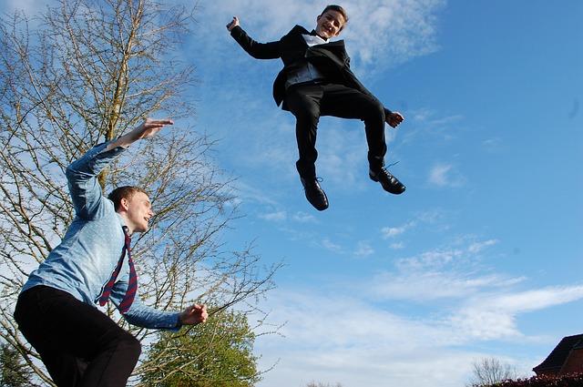 dva muži skákající na trampolíně