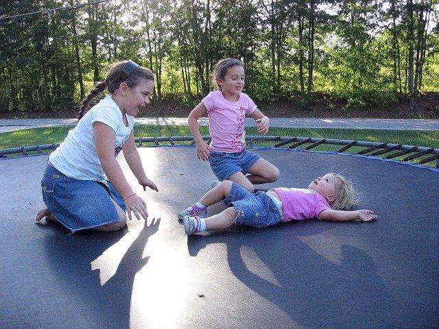děti sedící na trampolíně